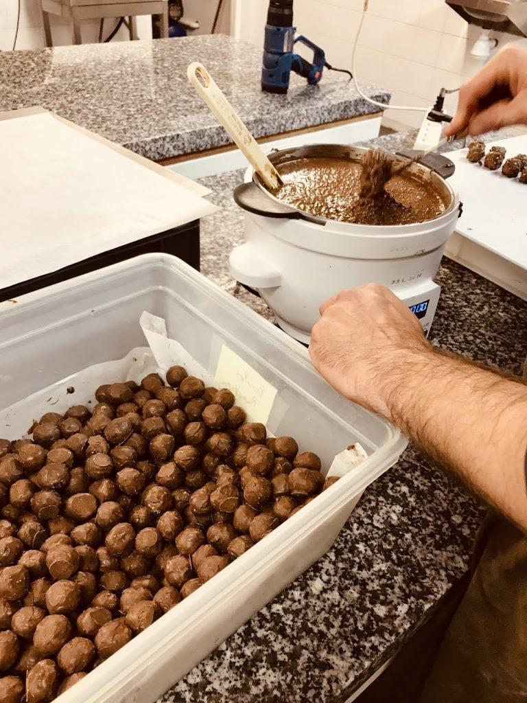 Enrobage à la main des rochers. Le chocolatier doit contrôler lui-même la courbe de cristallisation.