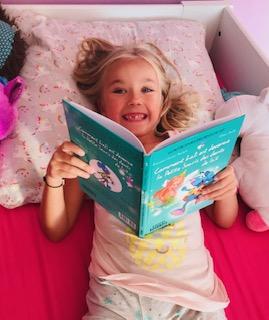 Mimi en pleine lecture de la Petite Souris avec des dents de lait en moins.